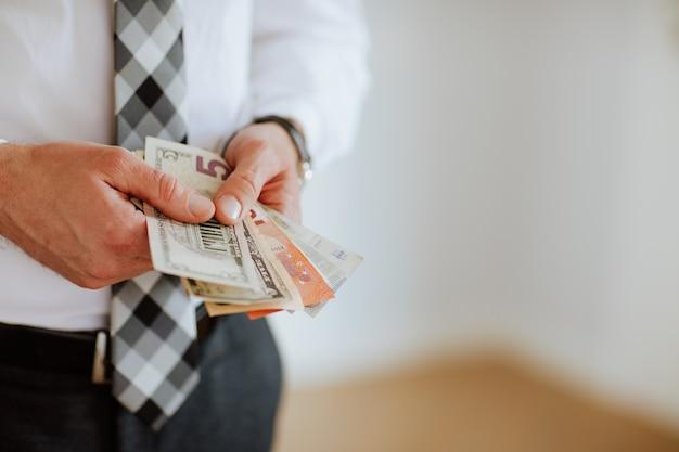 白い背景の上のユーロやドルのようなお金を保持している男の手。