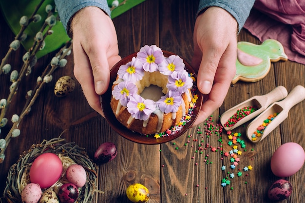 Man's hands holding ring cake decorated with flowers