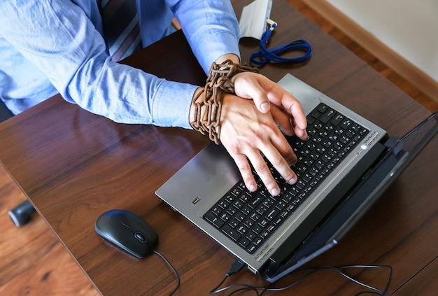 오래 된 녹슨 사슬에 남자의 손입니다. 사무의 함정에서. 일상적인 작업. 노트북 근처 관리자입니다.