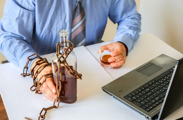병 근처에 오래 된 녹슨 사슬에 남자의 손. 알코올 중독. 사무의 함정에서. 일상적인 작업. 노트북 근처 관리자입니다.