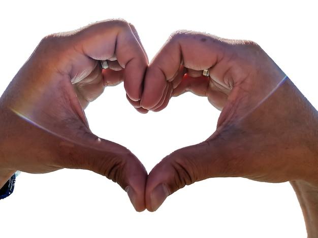 흰색 배경에 격리된 남자의 손은 사랑과 감정을 상징하는 심장으로 접혀 있습니다. 낭만주의 개념입니다.