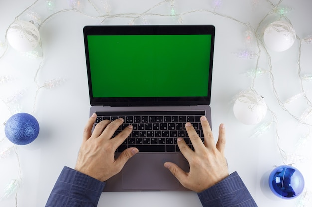 A man's hands and a laptop with a green screen