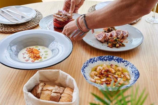 레스토랑의 나무 테이블에 음식 접시를 놓는 남자의 손