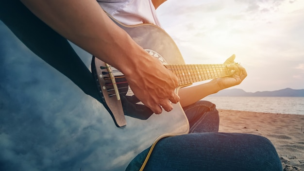 Man's hands playing acoustic guitar on the beach