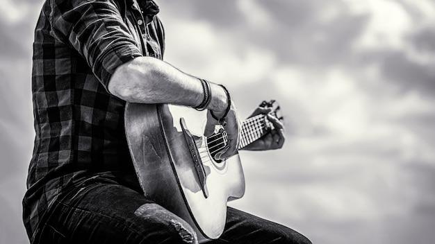 アコースティックギターを弾く男の手、クローズアップ。アコースティックギターの演奏。音楽のコンセプト。黒と白。