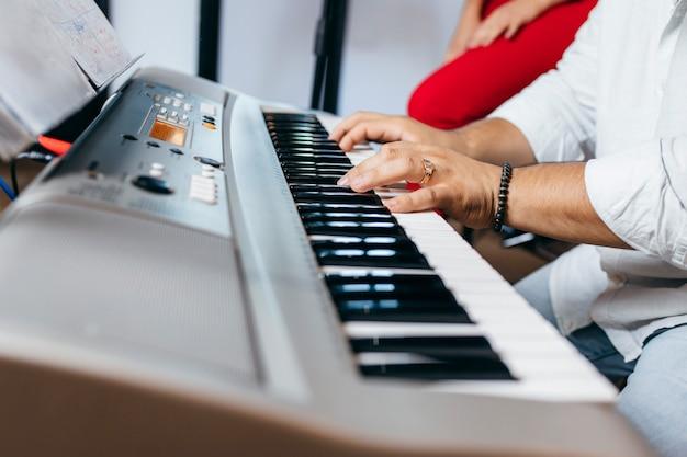 Мужские руки играют на синтезаторе