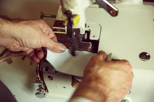 Mani dell'uomo dietro la cucitura. laboratorio di pelletteria. tessile industriale vintage. l'uomo nella professione femminile. concetto di uguaglianza di genere