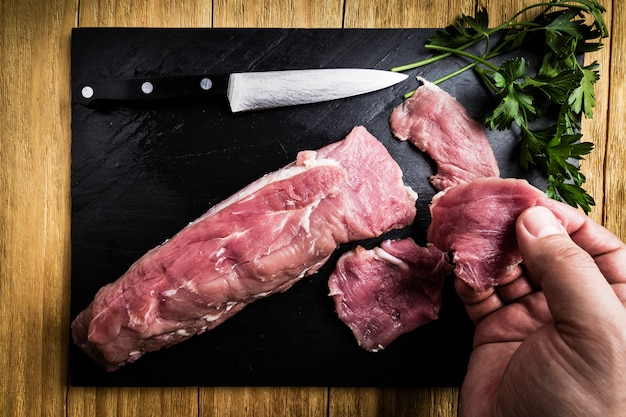 Man's hands splitting a pork tenderloin with a knife next to some parsley branches