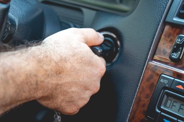 남자의 손에 엔진 자동차를 시작하는 열쇠를 가져갑니다.