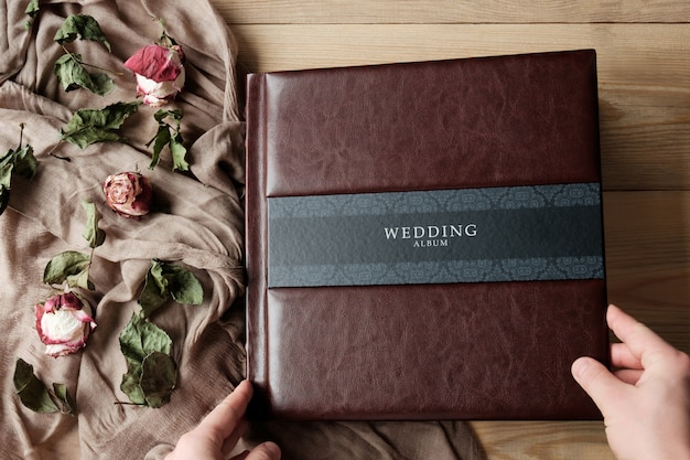 Man's hands touching leather covered wedding photo album