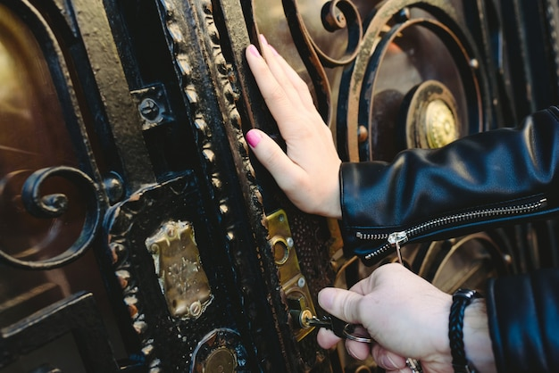 Man's hands trying to open a door by inserting the key into the lock.