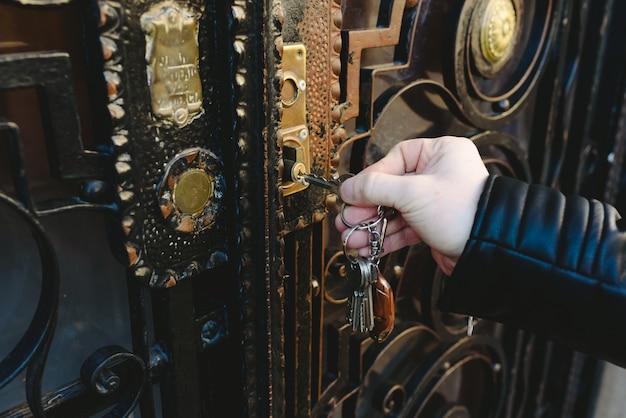 자물쇠에 열쇠를 삽입하여 문을 열려고하는 사람의 손.