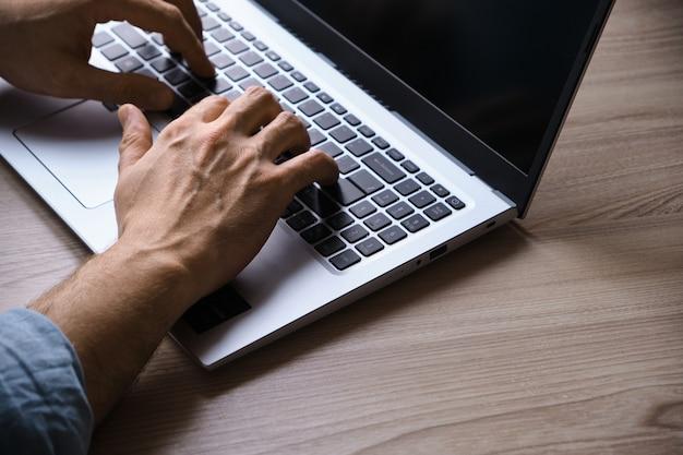 ノートパソコンのキーボードで入力する男の手