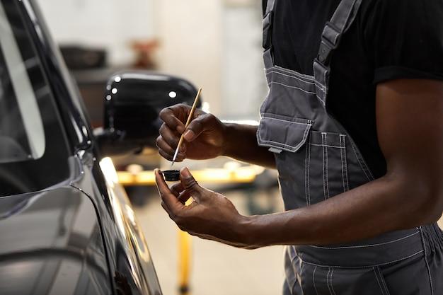 남자의 손에 세부 브러시를 사용하여 자동차 페인트