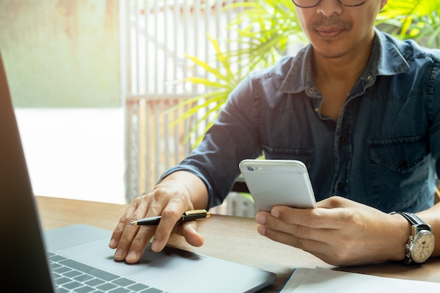 Man's hands using cell phone while working with laptop on wooden desk
