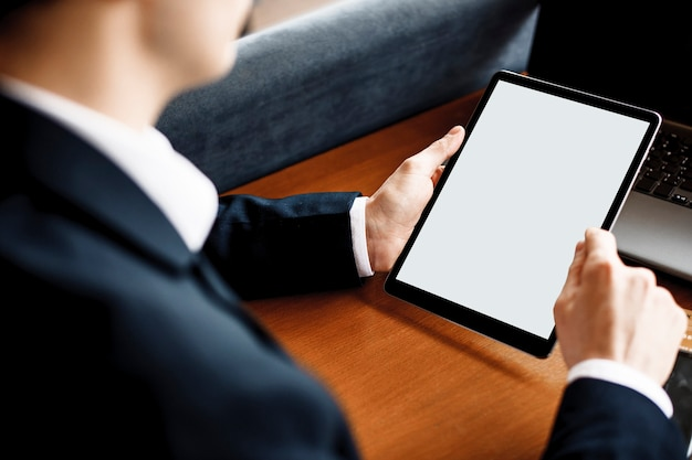 机に座ってタブレットを使用して男の手。