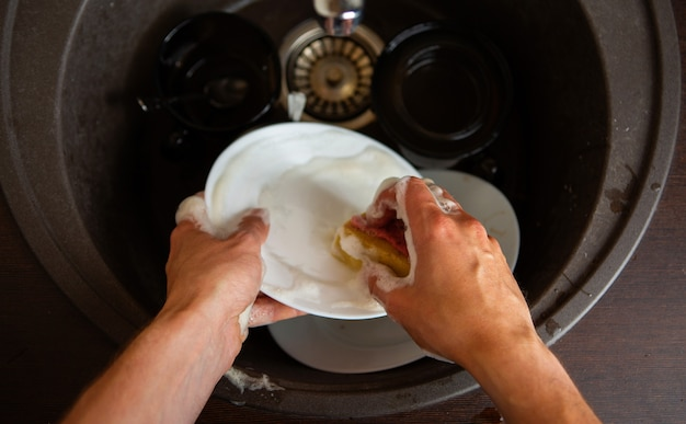 Man's hands washing the dish into sink in kitchen