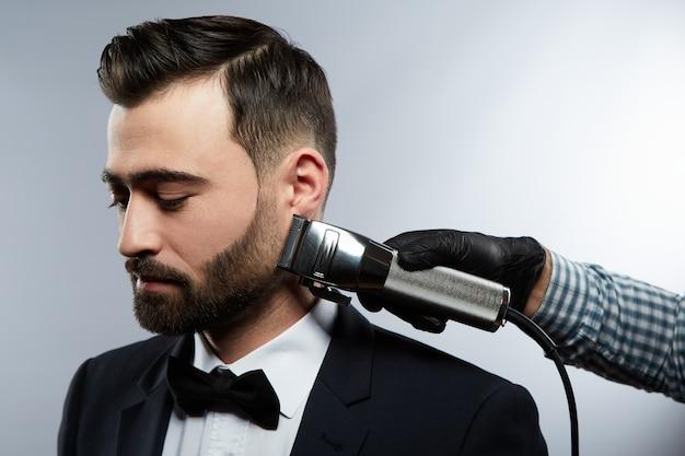 스튜디오 배경, 초상화, 가까이, 트리머, 이발소 개념에서 검은 머리를 가진 남자를위한 수염 형태를 만드는 셔츠를 입고 남자의 손.