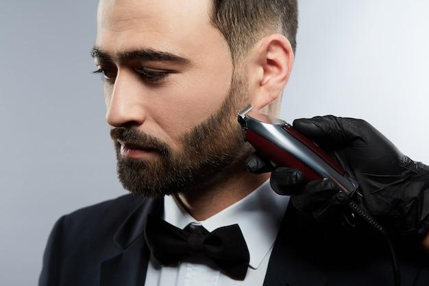 스튜디오 배경, 초상화, 가까이, 트리머에서 검은 머리를 가진 남자를위한 수염 형태를 만드는 셔츠를 입고 남자의 손.