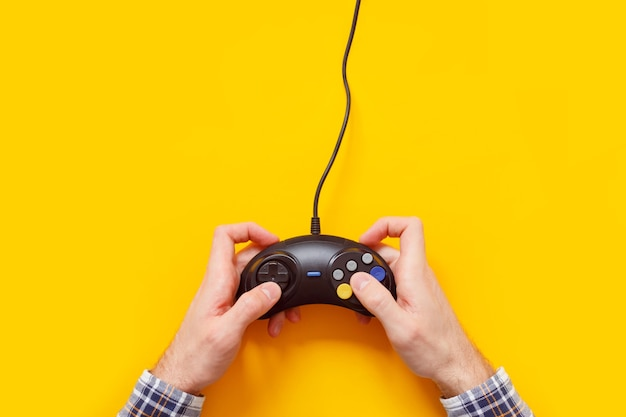 黄色で隔離の古い有線ゲームパッドと男の手