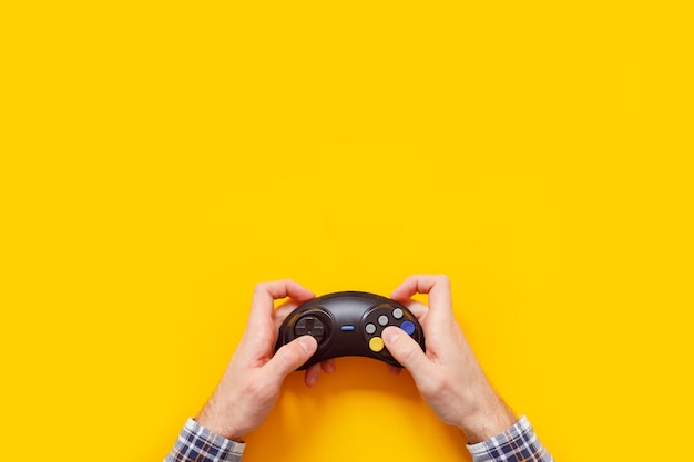 黄色で隔離のワイヤレスゲームパッドと男の手