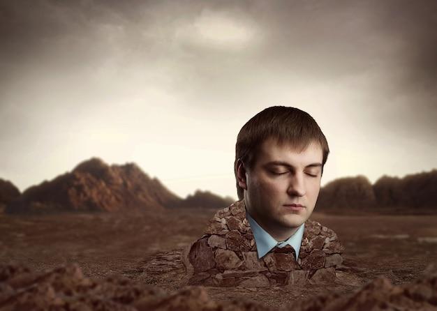 Голова человека встроена в кирпичи на фоне песчаных гор