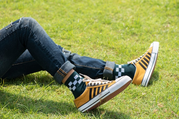 Man's legs in blue jeans and yellow sneakers on green grass.