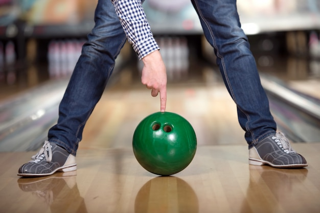Man's legs and green bowling ball.