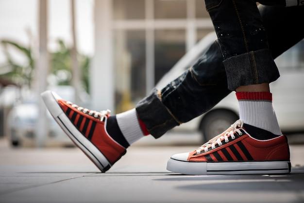 Мужские ножки в синих джинсах и оранжевых кроссовках.