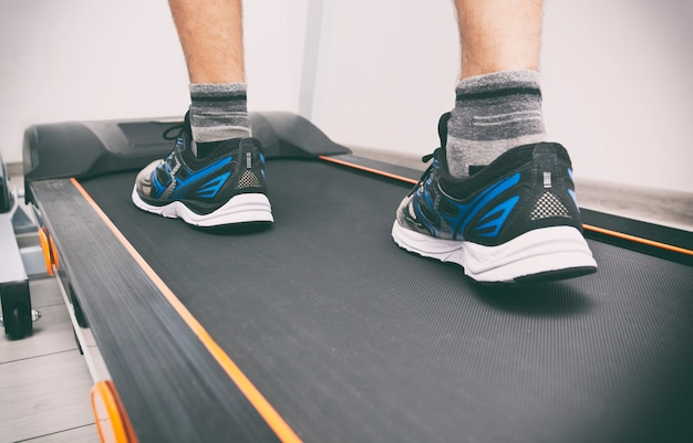 The man's legs in sneakers on the treadmill