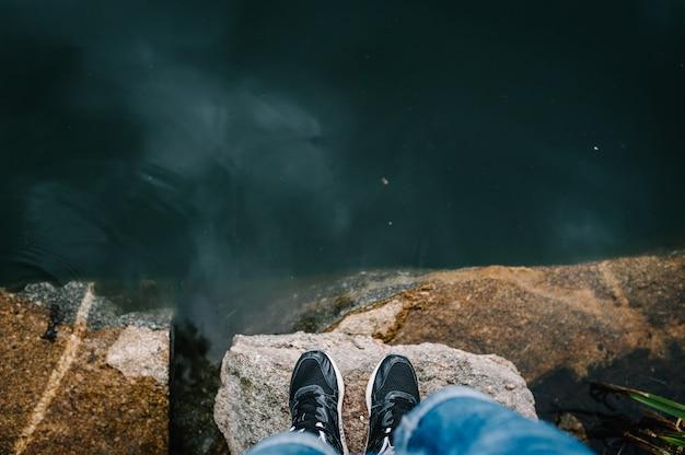湖の前の石の上に男の足が立っている