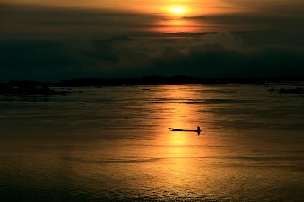 湖でボートの中の男のシルエット