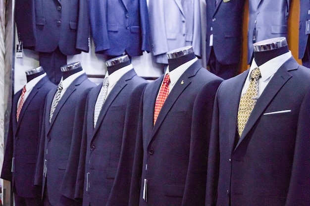 마네킹의 고전적인 스타일의 남자 정장은 현대적인 옷의 세련된 부티크에서 판매되고 있습니다.