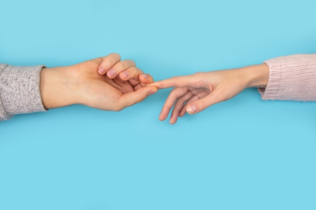 Man's and woman's hands keep each other on blue.