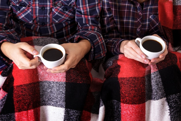 Man's and woman's hands keeps two cups of coffee in worm plaid.