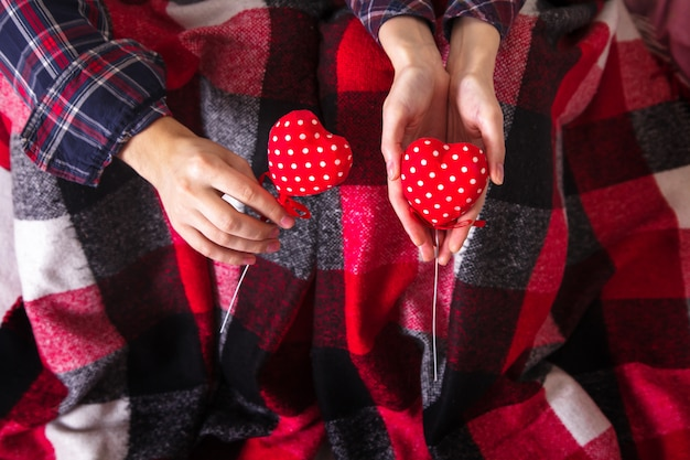 Man's and woman's hands keeps two red hearts in worm plaid.