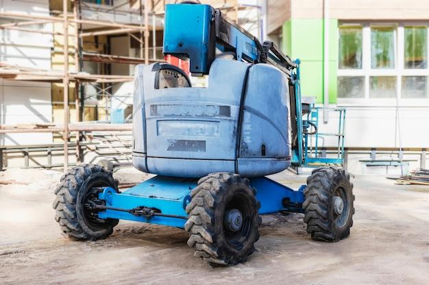 사람의 일은 고도에 있습니다. 건설 현장에서 작업자를 높은 높이로 들어올리기 위한 자체 추진 건설 메커니즘. 정상에서 안전한 작업.