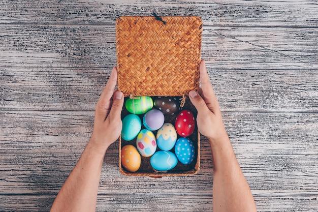 Плоские кладут пасхальные яйца в деревянной коробке с man_s руки на деревянных фоне.