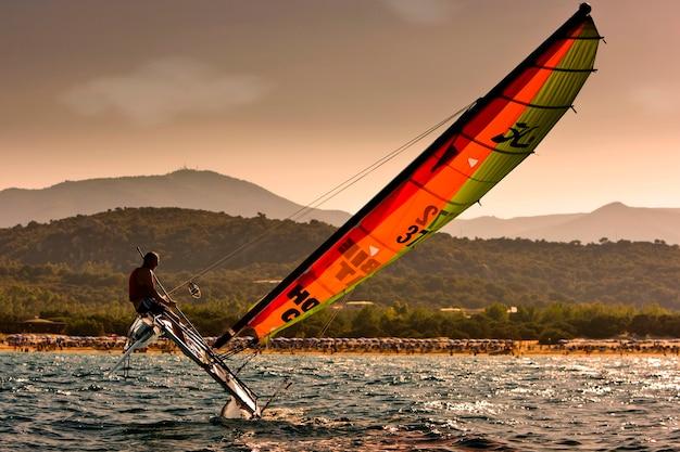 Man sailing catamaran in strong winds on ocean