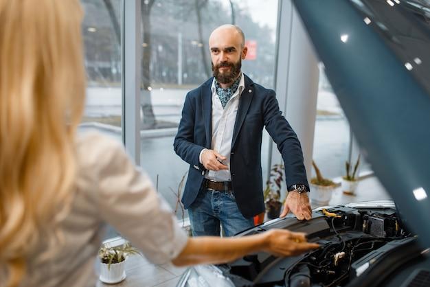 Man and saleslady choosing auto in car dealership