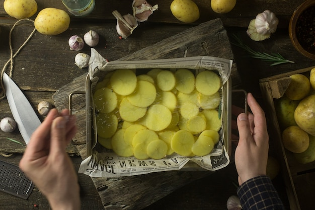 Man salt sliced potatoes for cooking on rustic wooden table