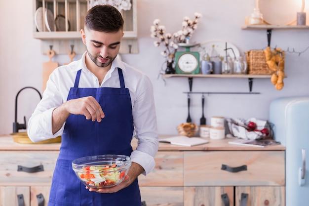 Man salting salad in bowl in kitchen