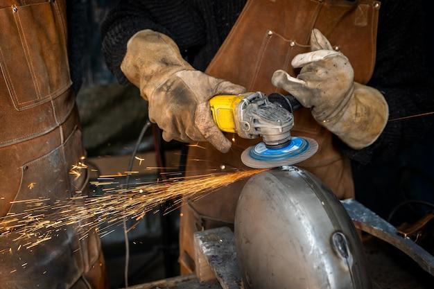 Человек шлифует металл, чтобы сделать металлический предмет