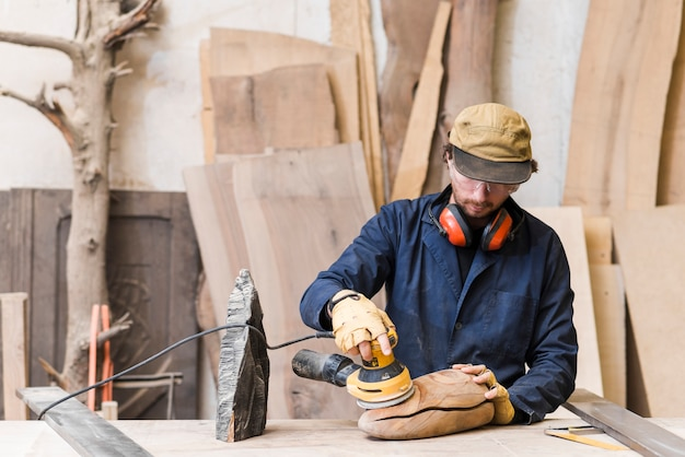 Man sanding a wood with orbital sander in a workshop