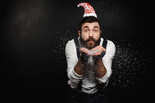 Man in santa claus hat blowing silver glitter over black.