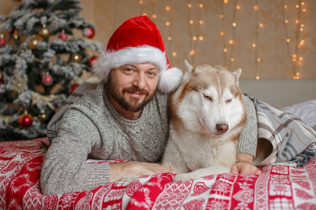 Man in a santa claus hat with a dog lie on the bed near the christmas tree