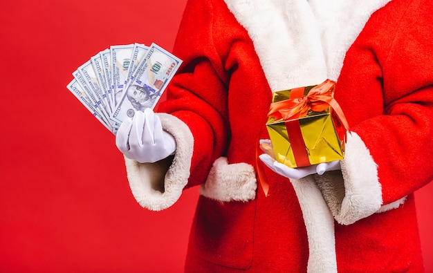 Man in santa claus holding money and gift box isolated on red background