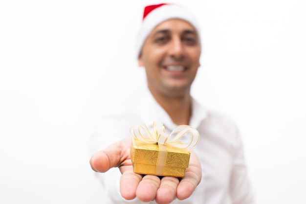 Man in santa hat holding small gift box on palm