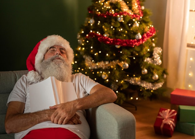 Man in santa hat sleeping on the sofa at home while holding book