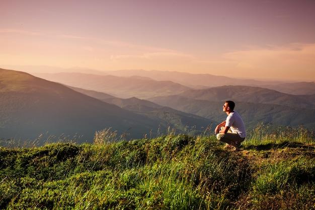 男は山の頂上に座った。自然と旅行のインスピレーション、モチベーションとコンセプトレタリングの背景